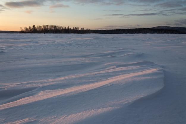 Mattina presto sul lago ghiacciato coperto di neve.