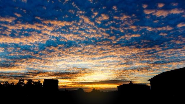 Cielo di alba multicolore di primo mattino con nuvole sopra il paesaggio urbano della siluetta