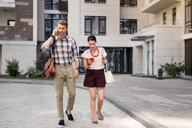 Mattina presto. giovani intelligenti che camminano insieme mentre vanno al lavoro