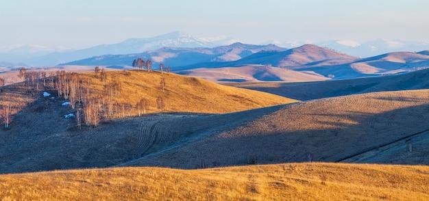Inizio della primavera, luce del tramonto sui pendii e sulle cime delle montagne, vista panoramica