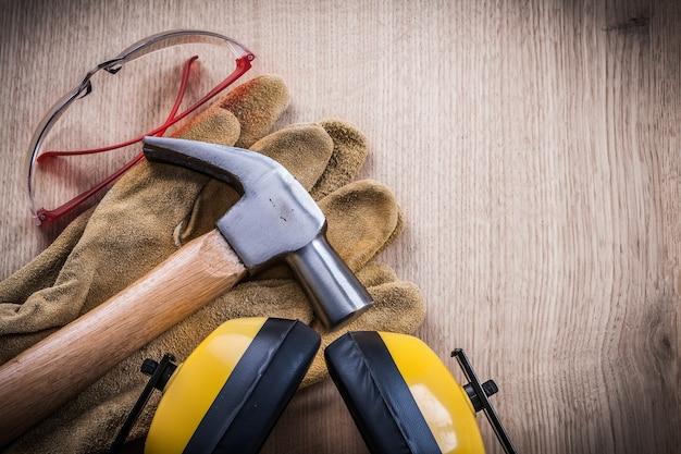 Paraorecchie martello guanti di sicurezza e occhiali di protezione su tavola di legno.