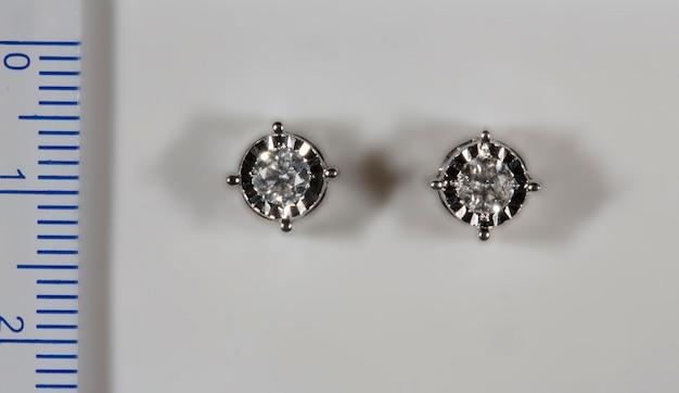 Orecchini realizzati in oro bianco con diamanti naturali accanto al righello i diamanti al centro sono ...