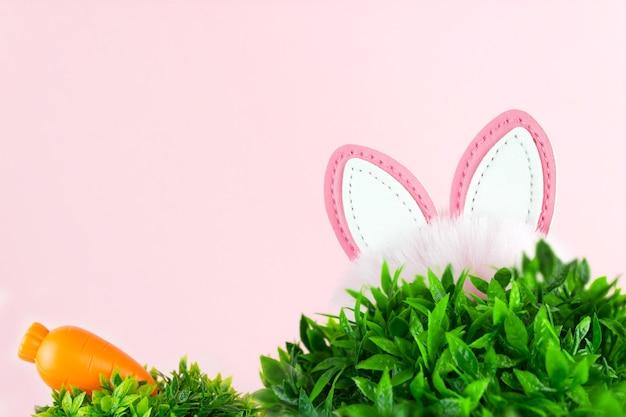 Orecchie di un coniglietto pasquale e di una carota sopra l'erba su sfondo rosa.