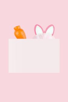 Orecchie di un coniglietto pasquale e di una carota su sfondo rosa. priorità bassa della lettera di pasqua. vacanze di primavera