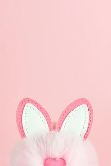 Orecchie di un coniglietto di pasqua su sfondo rosa.