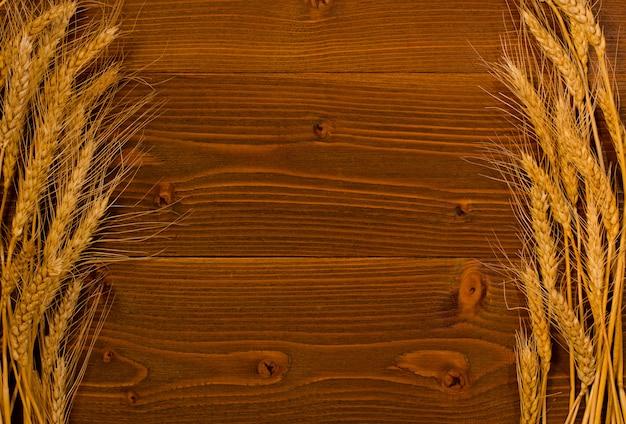 Spighe di grano maturo su entrambi i lati di un fondo di legno