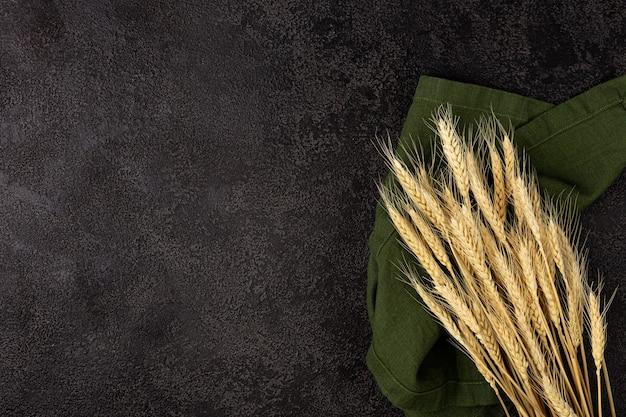 Spighe di grano sulla trama di sfondo nero. copyspace. vista dall'alto. spighe di grano su un tovagliolo di lino verde