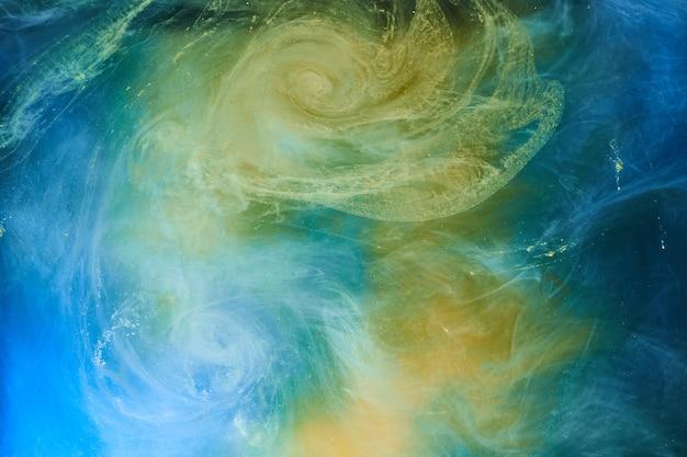 La terra colora lo sfondo astratto, il fumo colorato dipinge sott'acqua, l'inchiostro vorticoso nell'acqua, l'oceano blu del mare giallo dell'esopianeta
