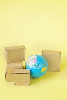 Il globo terrestre è circondato da scatole. commercio globale e trasporto internazionale di prodotti di merci. spedizioni merci, commercio mondiale ed economia. distribuzione, import export. fatturato merceologico.