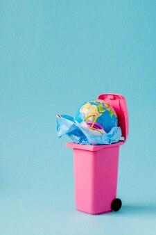 Il globo terrestre si trova nella spazzatura. il globo si trova in un mucchio di plastica. inquinamento plastico della natura