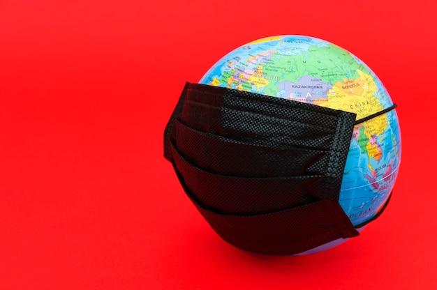 Modello di globo terrestre con mascherina chirurgica nera isolata su sfondo rosso