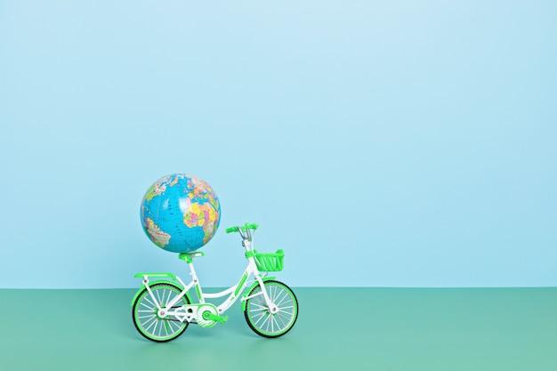 Globo terrestre in sella a una bicicletta verde su sfondo blu. giornata senza auto, giornata mondiale della bicicletta, protezione dell'ambiente, concetto di stile di vita sostenibile con spazio per le copie