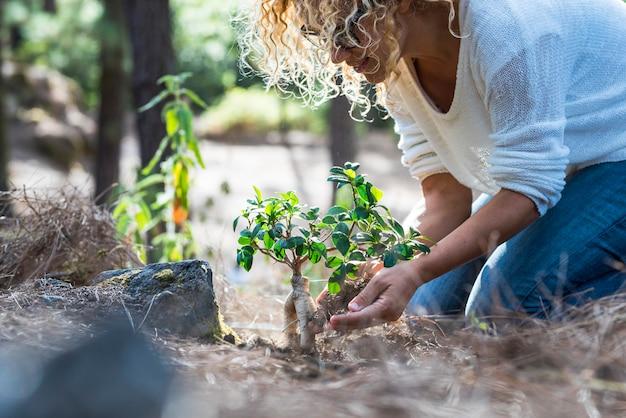 Concetto di celebrazione della giornata della terra con una donna felice che pianta un nuovo albero nella foresta