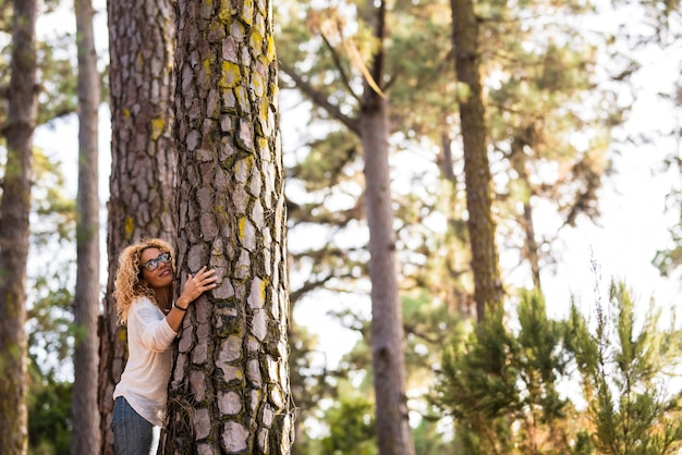 La giornata della terra salva il pianeta rispetta il mondo con una donna adulta che abbraccia un grande e bellissimo pino nella foresta