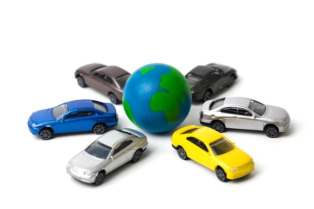Terra con auto in miniatura su bianco