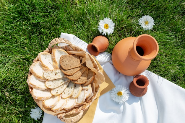 Una brocca di terracotta e del pane in un cesto. vista dall'alto