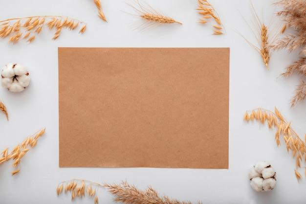 Modello di invito a nota di carta artigianale in bianco di colore beige terroso con cereali di fiori di cotone essiccato mockup. brown mockup notepad vuoto per biglietto di auguri. elegante copia spazio in cornice sfondo bianco.
