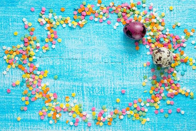 Zucchero del pasticcere del fondo di pasqua e uova di quaglia su una tavola di legno.