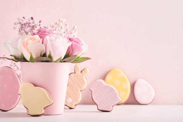 Decorazione di sfondo di pasqua con bellissimi fiori di rose rosa bouquet in vaso, uova di pasqua, coniglietto e pulcino sul tavolo sfondo rosa.