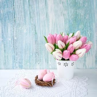Sfondo di pasqua. uova di pasqua decorative e tulipani rosa in vaso. copia spazio
