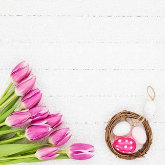 Sfondo di pasqua. tulipani rosa, uova di pasqua sulla tovaglia bianca. vista dall'alto, copia dello spazio