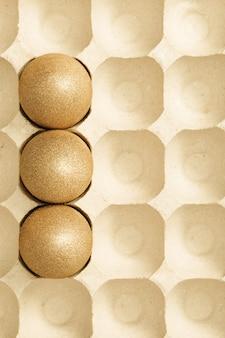 Sfondo di pasqua con uova luminose, uova colorate dorate lucide in imballaggi di cartone. pasqua laici piatta.