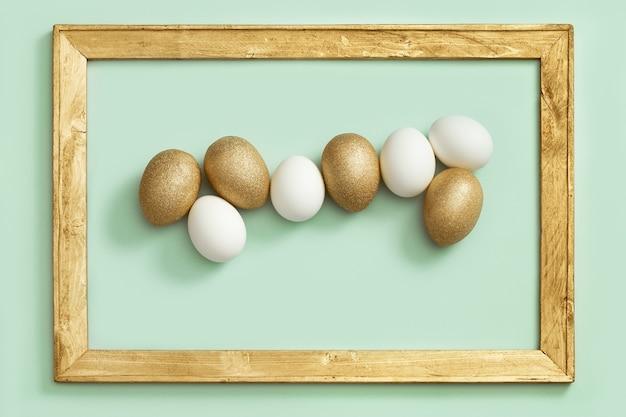 Sfondo di pasqua con uova luminose, uova colorate e bianche dorate lucide su carta verde in cornice di legno