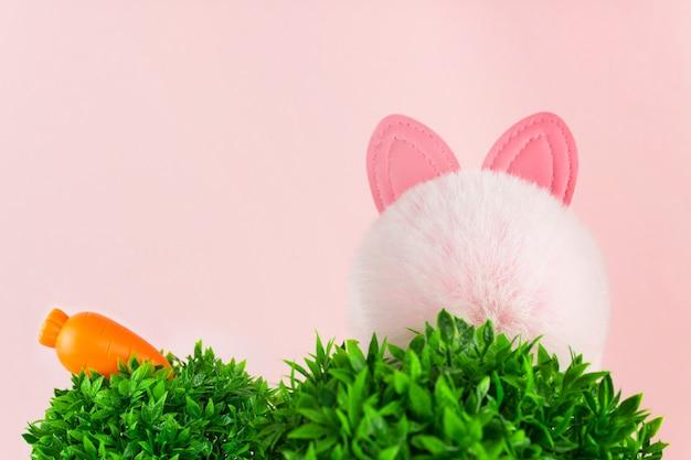 Sfondo pasquale con carota, orecchie da coniglio che si nascondono in un paesaggio erboso su sfondo rosa.