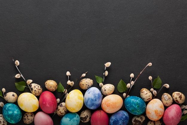 Sfondo di pasqua con uova colorate e rami con foglie verdi