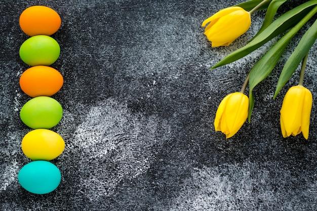 Sfondo di pasqua con spazio di copia. carta regalo pasquale con uova dipinte e tulipani gialli su sfondo nero scuro grunge.