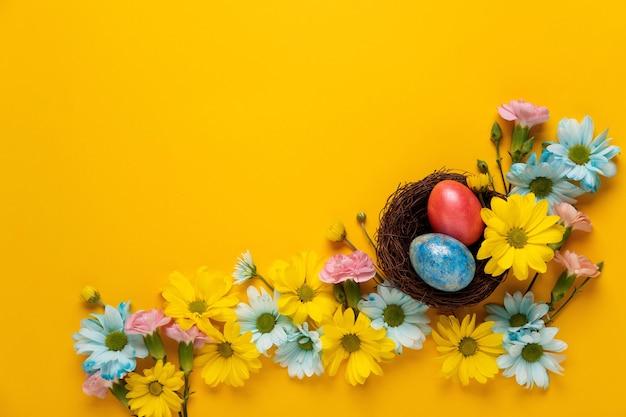 Sfondo di pasqua con uova di pasqua e fiori primaverili. lay piatto. modello di biglietto di auguri.