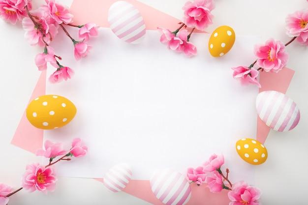 Sfondo di pasqua con uova di pasqua e fiori primaverili. vista dall'alto con copia spazio