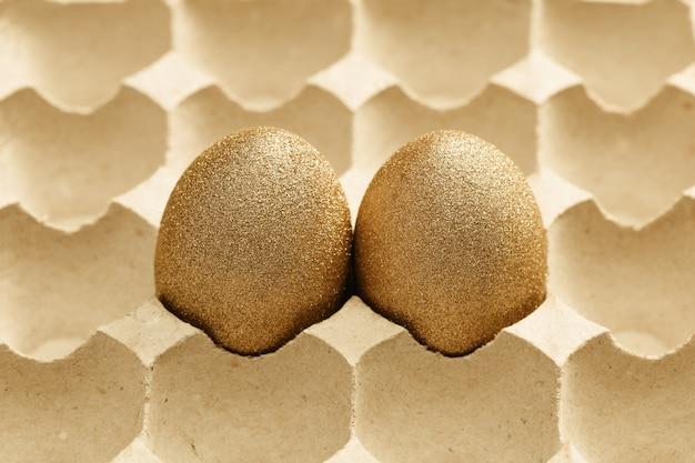 Sfondo di pasqua con due uova, uova colorate dorate lucide in imballaggi di cartone.