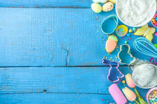 Sfondo di cottura di pasqua con mattarello, frusta, uova, farina e coriandoli di zucchero colorati
