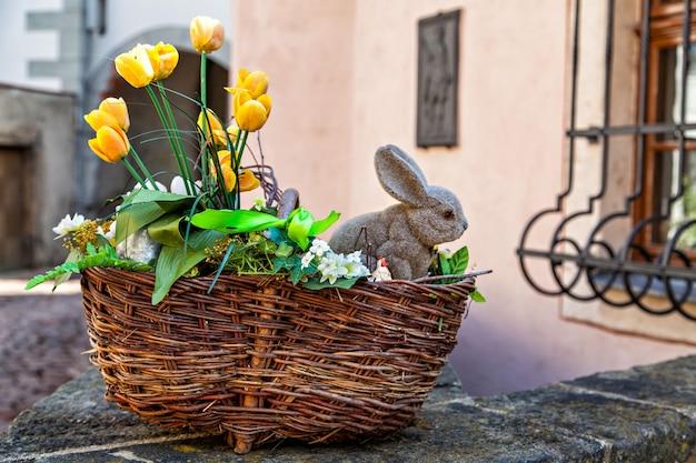 Cesto pasquale con fiori gialli e coniglietto, all'aperto