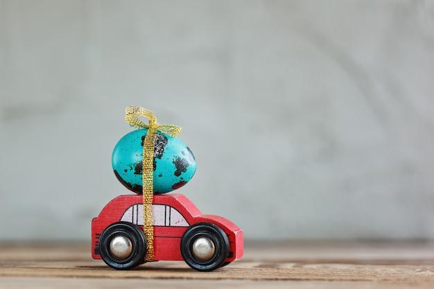 Uovo blu di pasqua sull'automobile rossa.