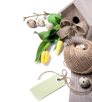 Bordo di pasqua con tulipani gialli e decorazioni naturali, lo spazio del testo