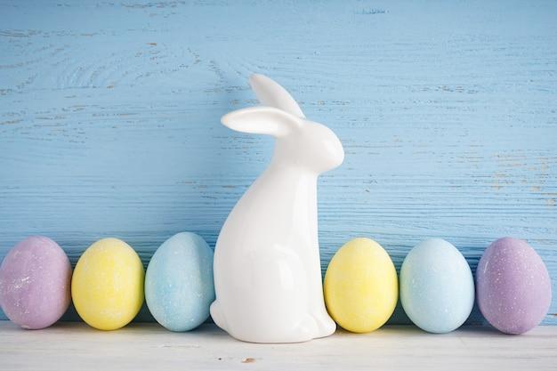 Coniglietto di pasqua e uova colorate su uno sfondo di legno viola