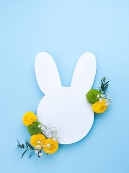 Coniglietto di pasqua da carta bianca con fiori in azzurro