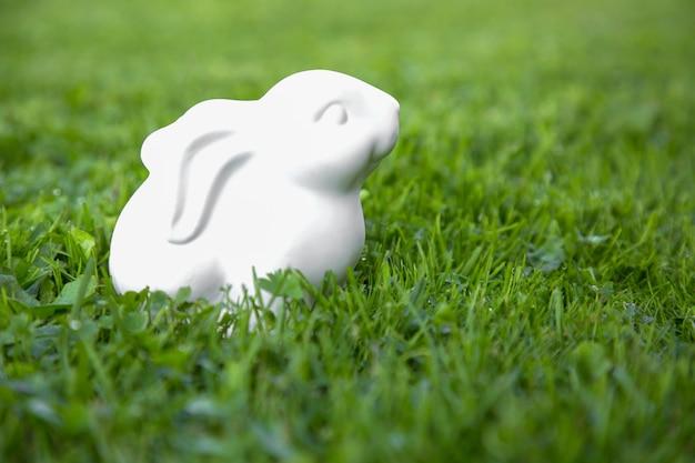 Statuetta di coniglio di coniglietto di pasqua sull'erba verde.