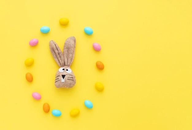 Coniglietto di pasqua con le uova di pasqua e il testo di pasqua felice. sfondo giallo.