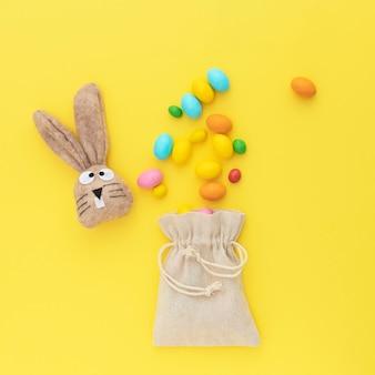 Coniglietto di pasqua con le uova di pasqua e buona pasqua. sfondo giallo.