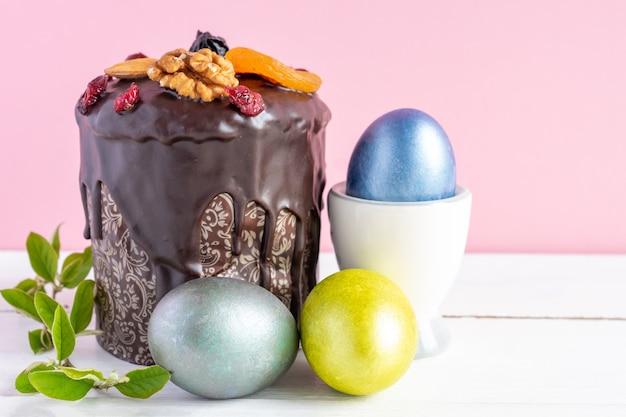 Torta di pasqua e uova colorate su sfondo rosa. cibo per le vacanze e concetto di pasqua.