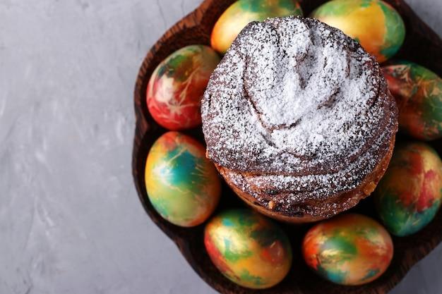 Torta di pasqua craffin e uova colorate in marmo sulla superficie grigia