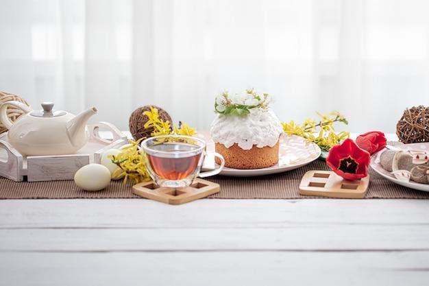 Torta di pasqua, uova, fiori e dettagli di arredamento sul tavolo. concetto di vacanza in famiglia di pasqua e messa in tavola.