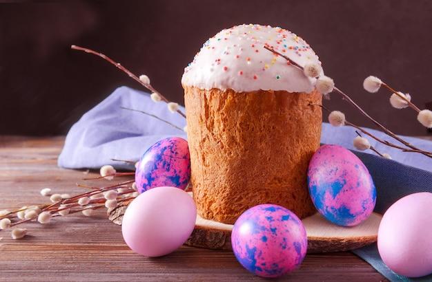Torta di pasqua con ramoscelli di salice e uova rosa e lilla su una superficie scura