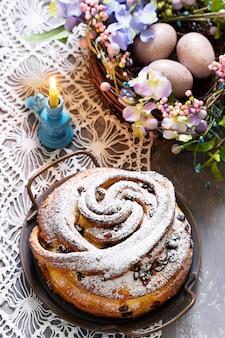 Torta pasquale con scorza e frutta secca e decoro pasquale su superficie chiara. stile rustico, messa a fuoco selettiva.