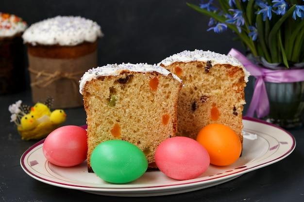 I dolci pasquali e le uova colorate si trovano su un piatto su una superficie scura, foto orizzontale