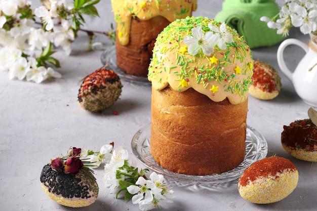 Dolci pasquali con glassa colorata e decorazione spolverata e uova pasquali decorate con spezie e cereali, formato orizzontale