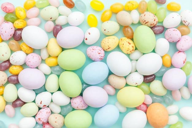 Uova di cioccolato della caramella di pasqua e dolci di gelatina isolati sulla tavola blu